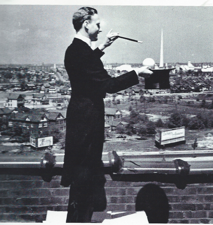 Magician Al Livingstone creating the illusion of producing the Trylon and Perisphere from his top hat.  Taken by Irving Desfor from a rooftop southwest of the Fair, probably in Forest Hills or Rego Park. Collection Queens Museum, courtesy of the Society of American Magicians.